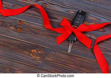 Car key with colorful bow on wooden background