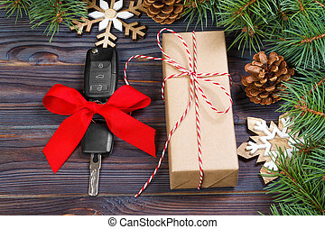 Car key with colorful bow with gift box and christmas decoration on wooden background