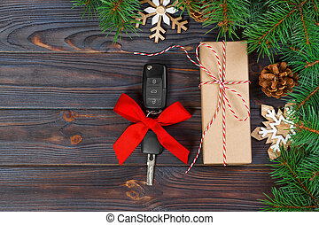 Car key with colorful bow with gift box on wooden background