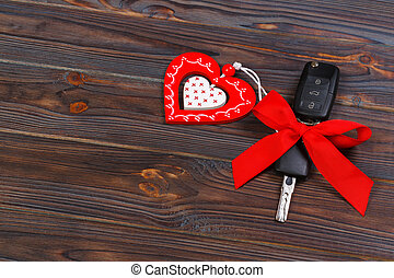 Car key with red heart on black natural background. ...