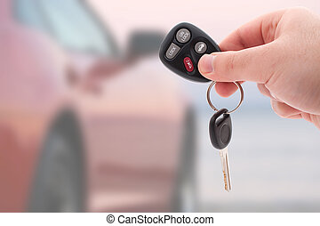 Car Keys and Remote - A hand holding car keys and a remote...