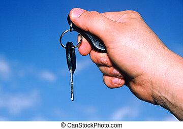 Hand holding car key against a blue sky