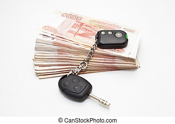 Car keys on stack of money on white