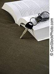 Car keys placed beside a book with a cloth backdrop.
