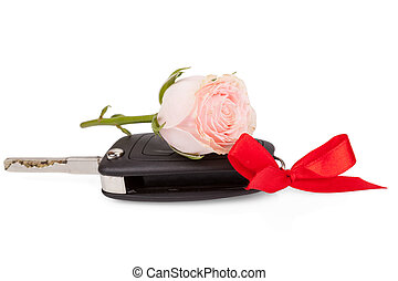 Car keys with ribbon and flowers as a gift isolated on white background