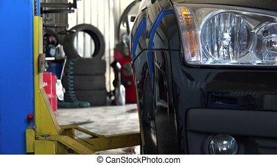 car lift up a car in service station garage. 4K