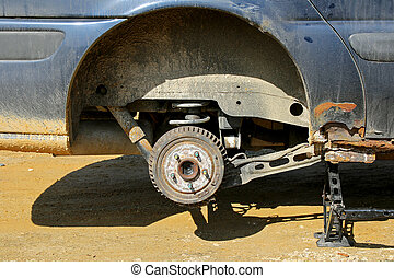 An old rusty automobile is lifted up on a jack with the wheel removed to change the tire.