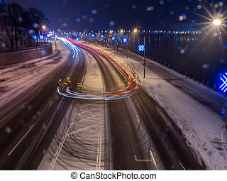 Car light at night on ice road in snow winter