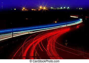 car light trails in red and white on night road curve