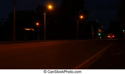 car lights in nighttime on a crossroad with traffic light,...