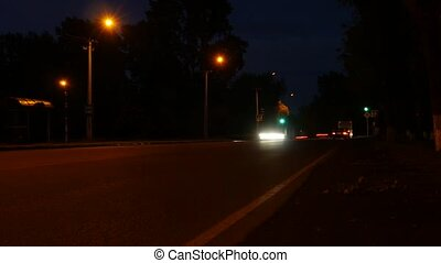 car lights in nighttime on a crossroad with traffic light, low traffic on an motorway junction