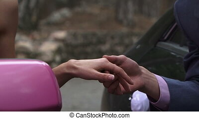 Car love - Beautiful man and woman holding hands looking out...