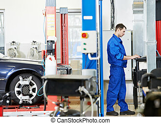 car mechanic at wheel alignment with computer