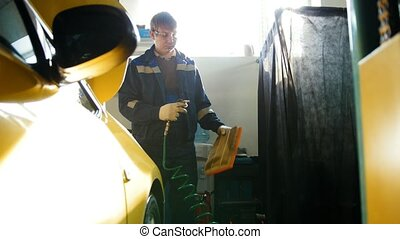Car mechanic blows air filter of automobile in service, telephoto