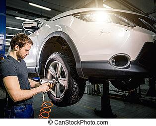 mechanic changing car wheel in auto repair garage