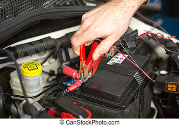 Mechatronic technician working on the battery of a car