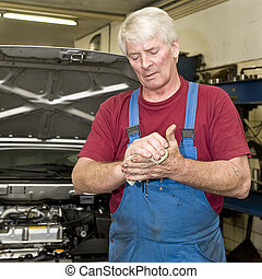 Car mechanic cleaning his hands - A motor mechanic cleaning...