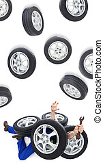 Car mechanic covered with tires