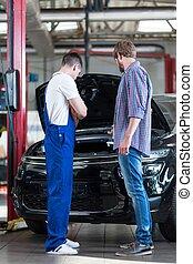 Car mechanic diagnosing auto