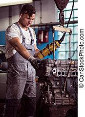 Car mechanic diagnosing broken engine
