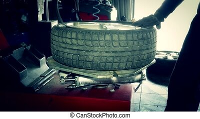 car mechanic dismount tire from wheel rim with special equipment.