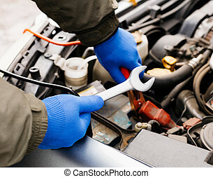 Car mechanic engineer using a wrench in process of fixing a car. Male hands of car mechanic with a wrench working in garage. Man in gloves working in car repair service station.