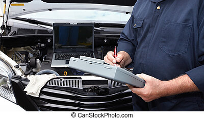 Car mechanic. - Hands of car mechanic with clipboard in auto...