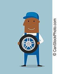 Car mechanic in blue uniform with wheel