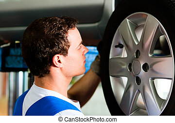 Car mechanic in workshop changing tire