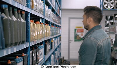 Car mechanic man choose modern car battery for truck at repair service station supermarket. A lot of goods.