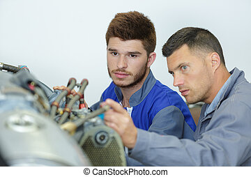 car mechanic man fixing the engine at the garage
