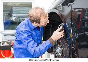 Car mechanic repairs the brakes of an automobile on a...