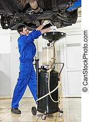 auto mechanic technician replacing and changing motor oil in automobile engine at maintenance repair service station