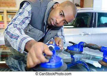 car mechanic replacing window