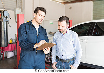 Car Mechanic Showing Maintenance Checklist To Customer In Garage