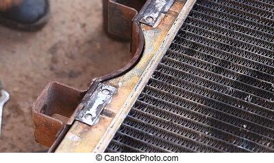 car mechanic solder radiator, radiator closeup repair