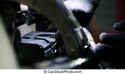 Car mechanic unscrewing battery of automobile in service, close up