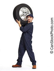 Car mechanic with a tire. - Smiling car mechanic with a tire...
