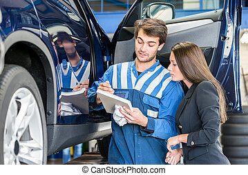 Car Mechanic With Customer Going Through Maintenance Checklist