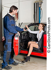Car mechanic with female customer