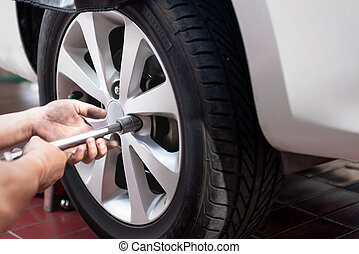 Car mechanic with spanner repair the tire