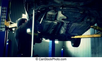 car mechanic with spanner tighten car suspension detail of lifted automobile