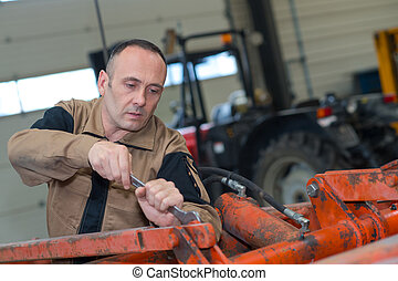 car mechanic with wrench working on farming machine