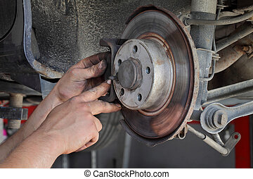 Car mechanic working on disc brakes