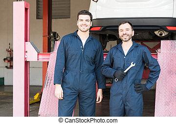 Car Mechanics In Coveralls Standing In Garage
