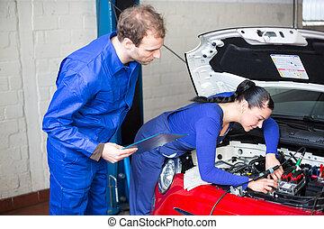 Car mechanics repairing the electrics