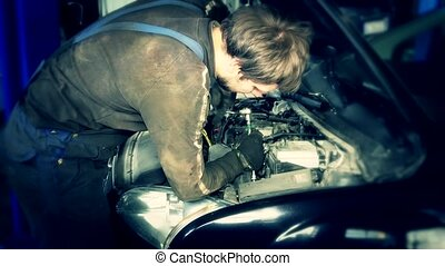 car mechanics with a spanner checking engine under hood in car service station