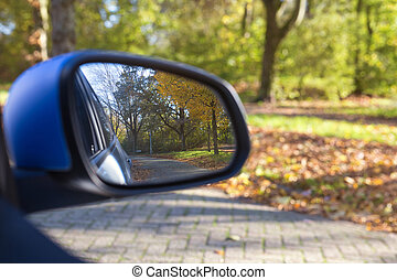 Car mirror Closeup with beautiful autumn landscape in reflection, on the road with the car on empty road blurred background