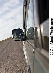 Car mirror in motion on the road