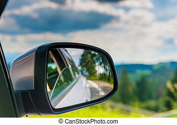 car mirror with reflection of a beautiful landscape in it, close-up